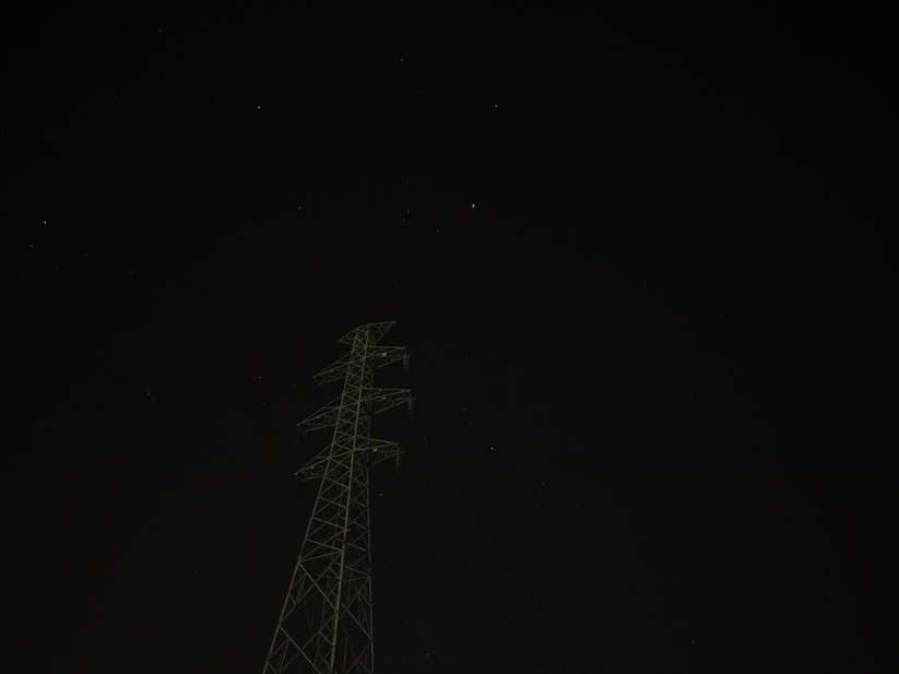 An electricity pylon at night with stars in the background